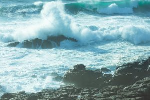 ola del mar chocando contra una roca en corrubedo, galicia