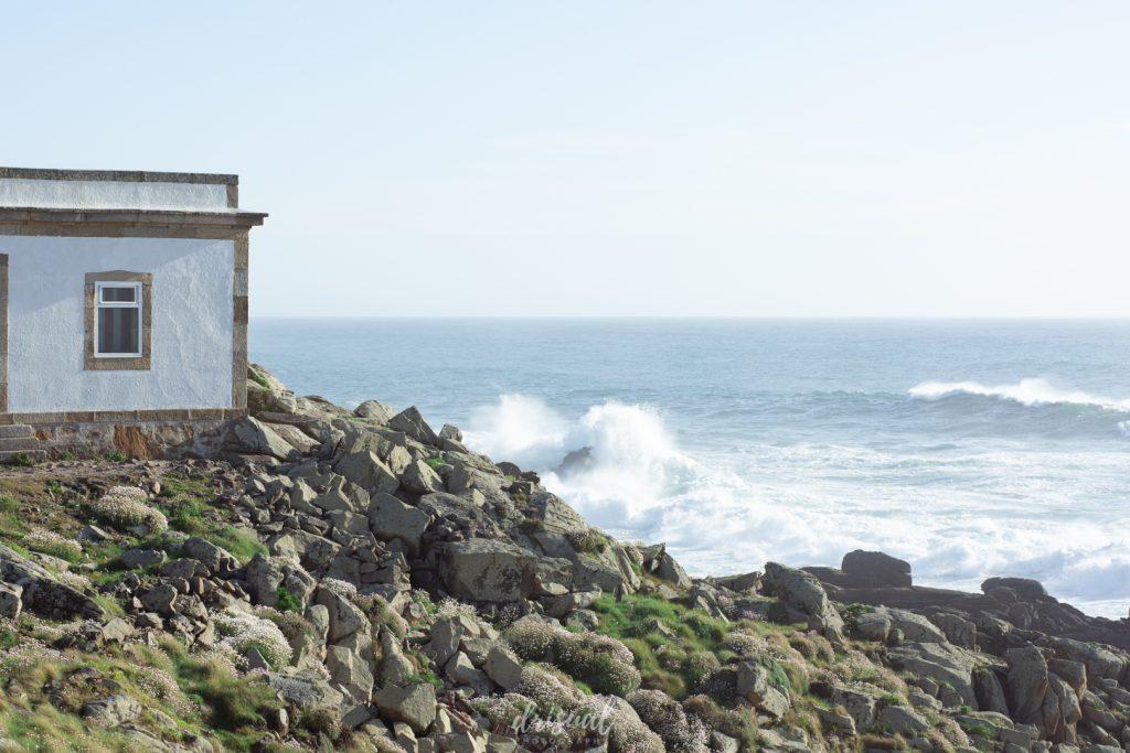 edificio del faro de corrubedo con las olas de mar rompiendo al fondo